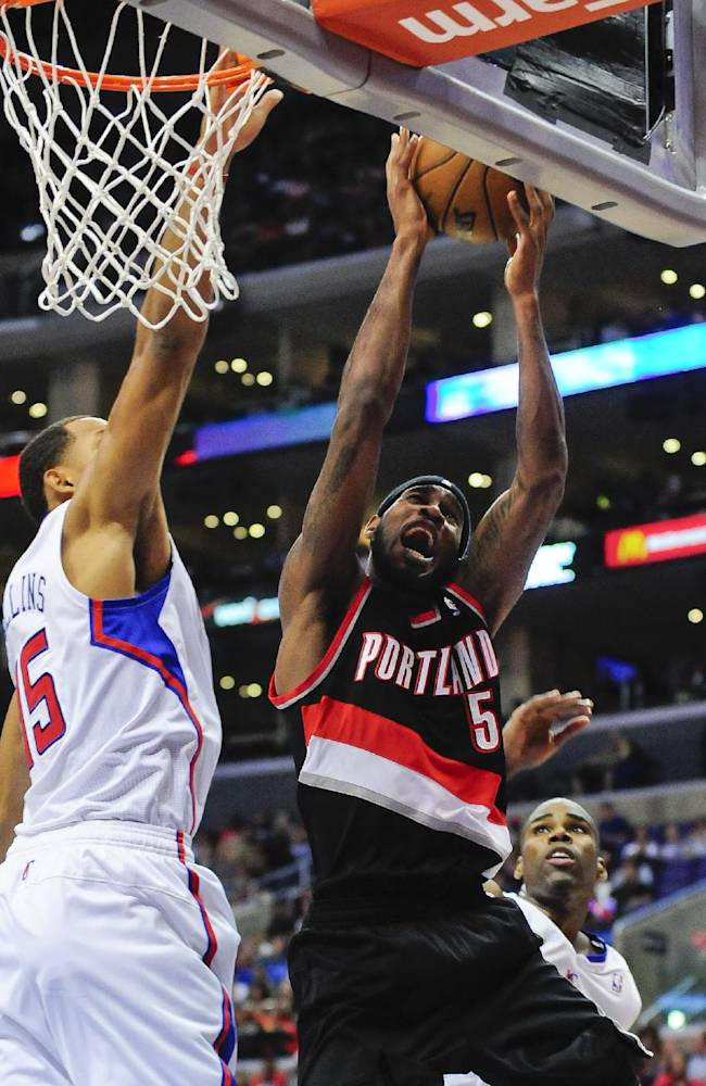 Portland Trail Blazers guard Will Barton (5) battles Los Angeles Clippers center Ryan Hollins (15) as he goes to the basket in the first half of a pre-season NBA basketball game, Friday, Oct. 18, 2013, in Los Angeles