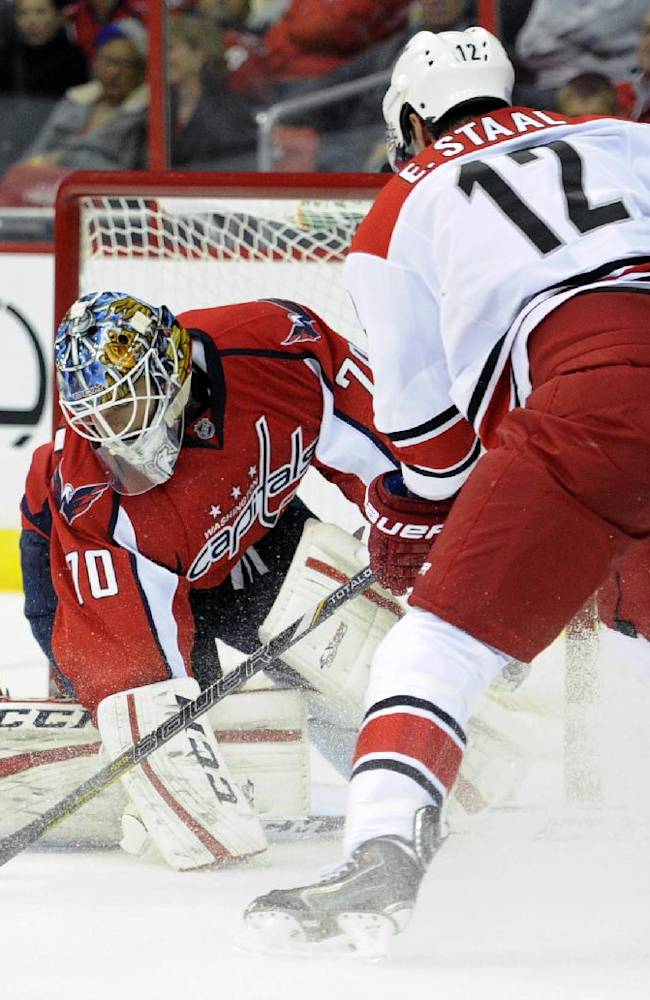 Carolina Hurricanes center Eric Staal (12) tries to get the puck past Washington Capitals goalie Braden Holtby (70) during the second period an NHL hockey game, Thursday, Oct. 10, 2013, in Washington