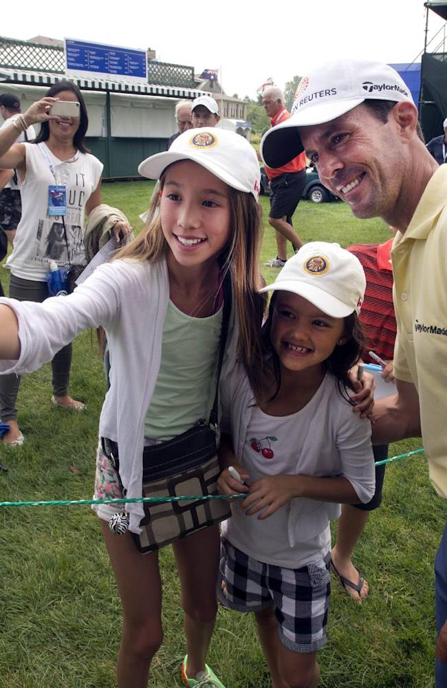 Canada's Mike Weir, of Canada, poses for a selfie with Kaylee Chin, left, and Maya Cunningham, center, during the pro-am event at the Canadian Open golf championship Wednesday, July 23, 2014 at Royal Montreal golf club in Montreal