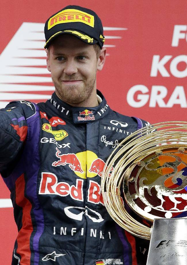 Red Bull driver Sebastian Vettel of Germany gestures as he celebrates on the podium after winning the Korean Formula One Grand Prix at the Korean International Circuit in Yeongam, South Korea, Sunday, Oct. 6, 2013