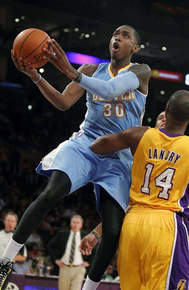 Denver Nuggets forward Quincy Miller, left, leaps towards the basket with Los Angeles Lakers forward Marcus Landry (14) defending in the fourth quarter of an NBA preseason basketball game Sunday, Oct. 6, 2013 in Los Angeles. The Nuggets won 97-88