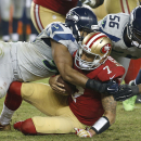 San Francisco 49ers quarterback Colin Kaepernick (7) is sacked by Seattle Seahawks outside linebacker K.J. Wright, left, as defensive end Cliff Avril (56) approaches during the fourth quarter of an NFL football game in Santa Clara, Calif., Thursday, Nov.