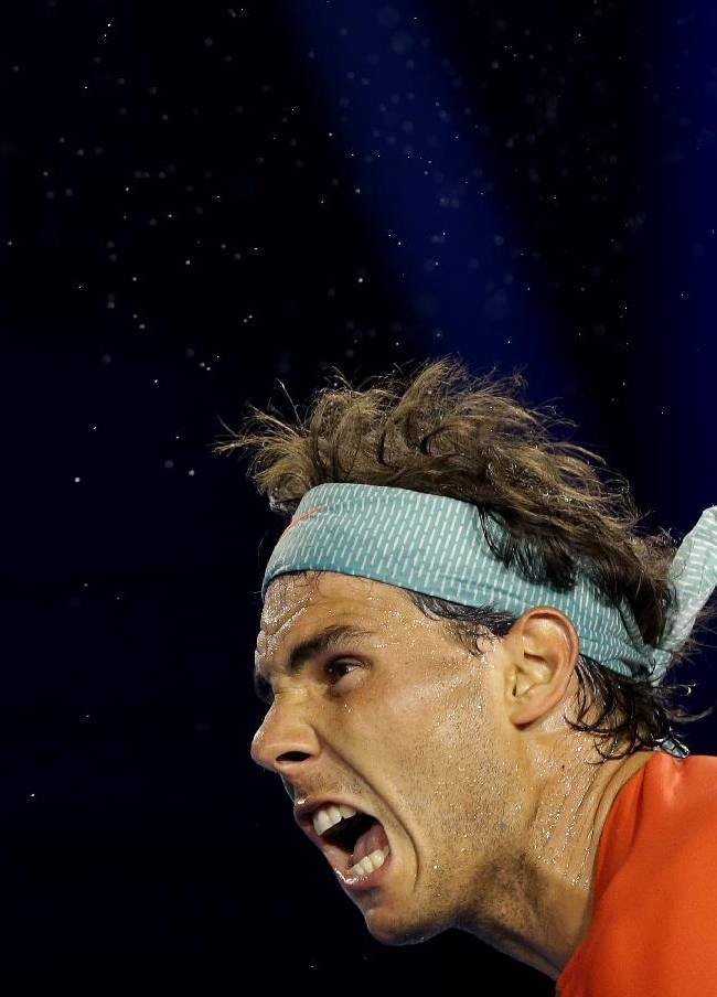 The sweat flies from Rafael Nadal of Spain as he serves to Thanasi Kokkinakis of Australia during their second round match at the Australian Open tennis championship in Melbourne, Australia, Thursday, Jan. 16, 2014