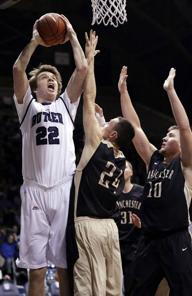 Butler center Nolan Berry, left, shoots over Manchester forward Jarod Schrock (24) and guard Grant Newlin in the first half of an NCAA college basketball game in Indianapolis, Monday, Dec. 9, 2013