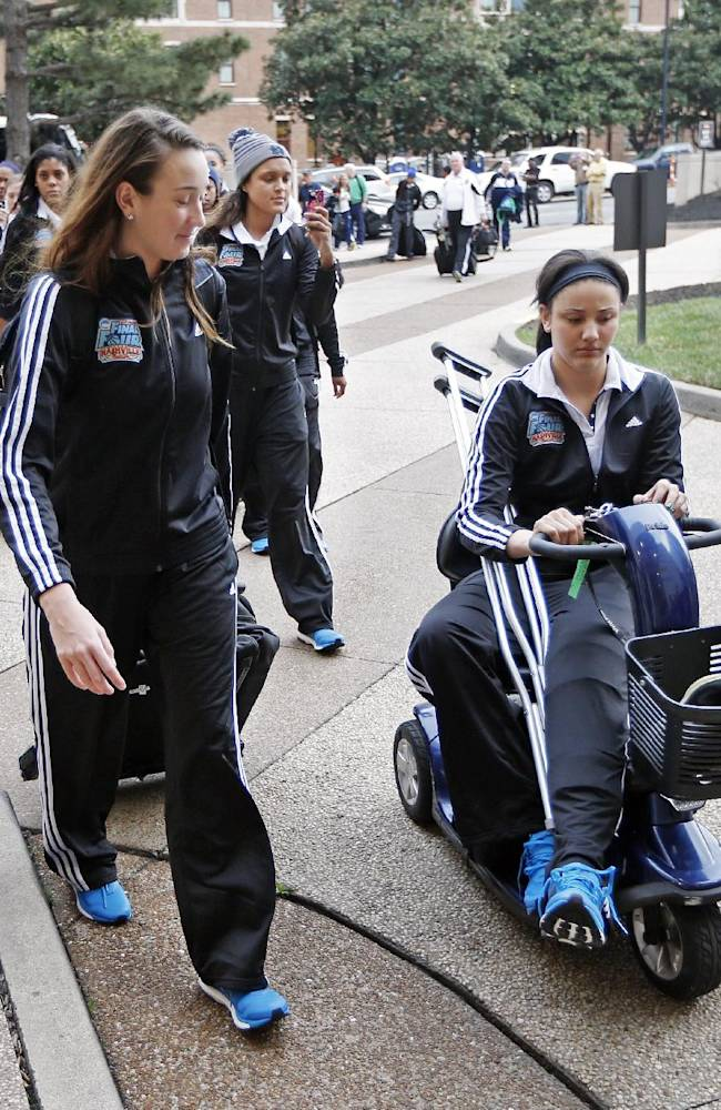 Injured forward Natalie Achonwa, right, arrives with teammates at a hotel for the NCAA women's Final Four college basketball tournament Thursday, April 3, 2014, in Nashville, Tenn. Notre Dame is scheduled to play Maryland in a semifinal on Sunday