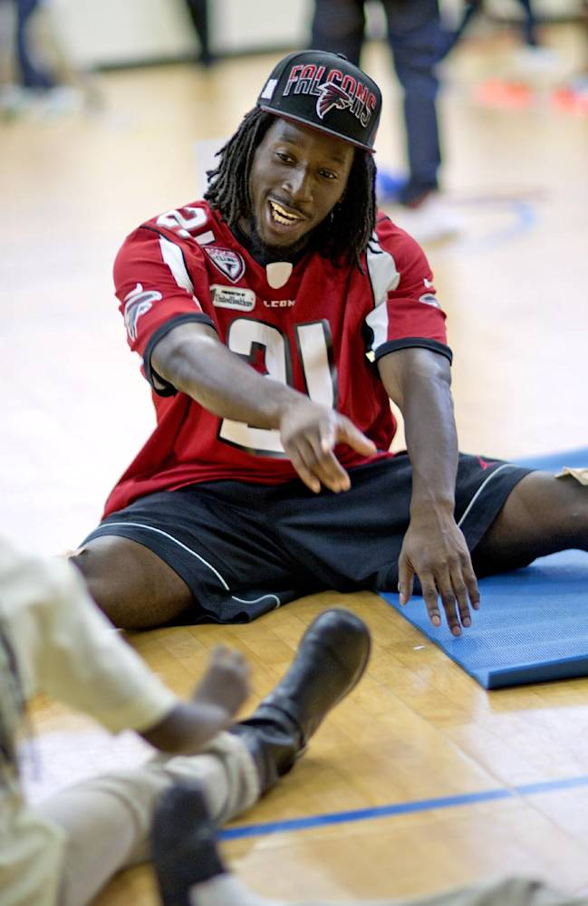 Atlanta Falcons' Desmond Trufant stretches with students from M. Agnes Jones Elementary School as the NFL football team takes part in the volunteer project,