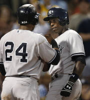 New York Yankees' Alfonso Soriano is greeted at home by Robinson Cano (24) after his three-run home run against the Boston Red Sox during the third inning of a baseball game at Fenway Park in Boston on Friday, Aug. 16, 2013. (AP Photo/Winslow Townson)