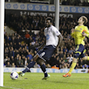 Tottenham's Emmanuel Adebayor, left, scores a goal ahead of Sunderland's Marcos Alonso during the English Premier League soccer match between Tottenham Hotspur and Sunderland at White Hart Lane stadium in London, Monday, April 7, 2014