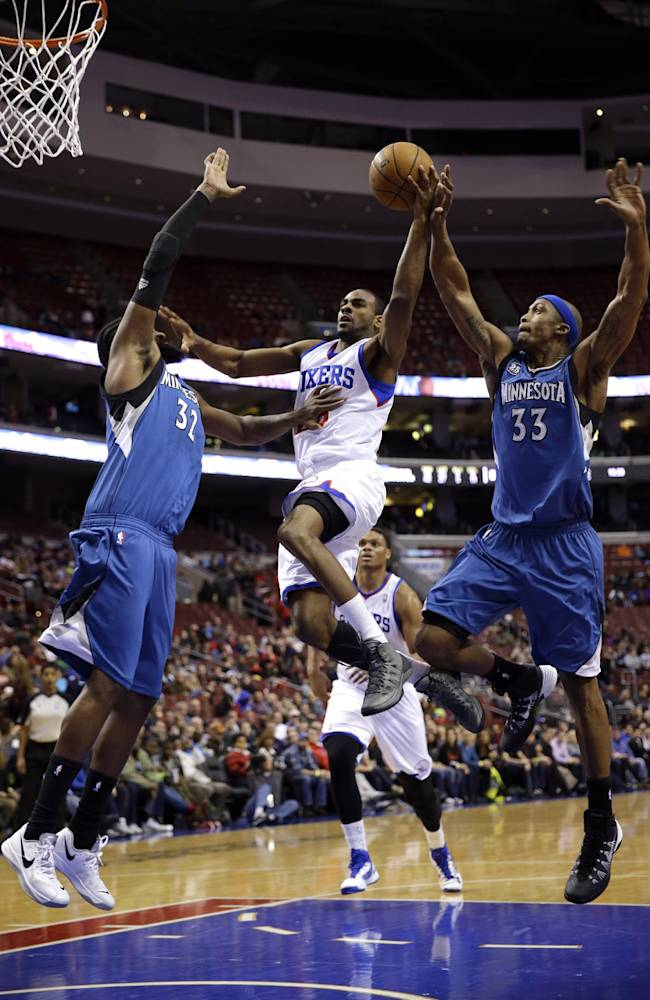 Philadelphia 76ers' Elliot Williams, center, goes up for a shot between Minnesota Timberwolves' Ronny Turiaf,  left, of France, and Dante Cunningham during the second half of an NBA basketball game, Monday, Jan. 6, 2014, in Philadelphia. Minnesota won 126-95