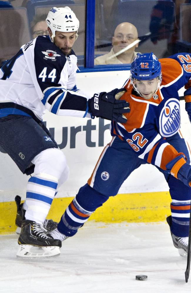 Winnipeg Jets' Zach Bogosian, left, and Edmonton Oilers' Mark Arcobello vie for the puck in the corner during the first period of an NHL hockey preseason game Monday, Sept. 23, 2013, in Edmonton, Alberta