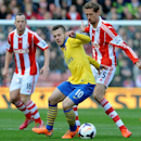 Arsenal's Jack Wilshere, centre, shields the bal from Stoke's Peter Crouch during the English Premier League soccer match between Stoke City and Arsenal at Britannia Stadium in Stoke On Trent, England, Saturday, March 1, 2014