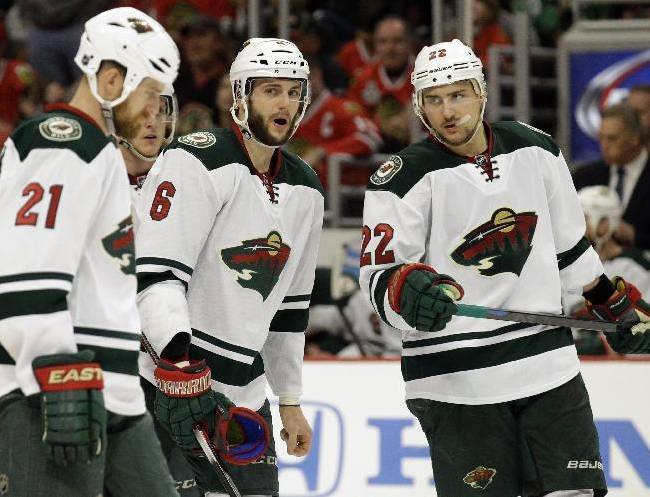 Minnesota Wild's Marco Scandella (6) talks to Kyle Brodziak (21) and Nino Niederreiter (22) during the second period in Game 2 of an NHL hockey second-round playoff series against the Chicago Blackhawks in Chicago, Sunday, May 4, 2014. The Blackhawks won 4-1