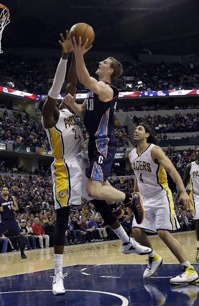 Charlotte Bobcats center Cody Zeller, center, shoots over Indiana Pacers center Ian Mahinmi during the first half of an NBA basketball game in Indianapolis, Friday, Dec. 13, 2013