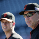 San Francisco Giants manager Bruce Bochy, right, watches batting practice alongside Buster Posey, at left, during a team workout on Saturday, Oct. 18, 2014, in San Francisco. The Giants are scheduled to play the Kansas City Royals in Game 1 of baseball's World Series on Tuesday, Oct. 21, in Kansas City. (AP Photo/Marcio Jose Sanchez)