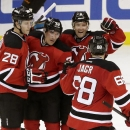 New Jersey Devils, from left, Damon Severson, Mike Cammalleri, Andy Greene and Jaromir Jagr, of the Czech Republic, celebrate a goal by Cammalleri against the San Jose Sharks during the third period of an NHL hockey game, Saturday, Oct. 18, 2014, in Newar