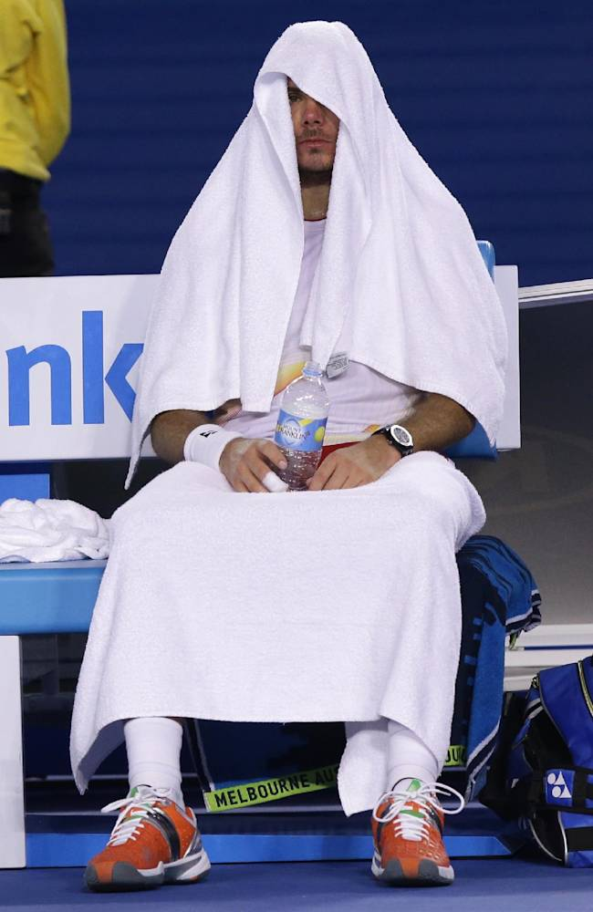 Stanislas Wawrinka of Switzerland covers himself with towels during a break in his quarterfinal against Novak Djokovic of Serbia during their quarterfinal at the Australian Open tennis championship in Melbourne, Australia, Tuesday, Jan. 21, 2014