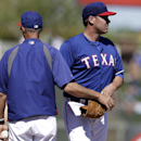 Texas Rangers pitching coach Mike Maddux, left, takes the ball from starter Colby Lewis in the first inning of a spring training exhibition baseball game against the Cleveland Indians, Monday, March 3, 2014, in Surprise , Ariz. Lewis was replaced in the f