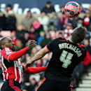 Sunderland's Jermain Defoe, left, vies for the ball with Fulham's Shaun Hutchinson, right, during their English FA Cup fourth round soccer match between Sunderland and Fulham at the Stadium of Light, Sunderland, England, Saturday, Jan. 24, 2015