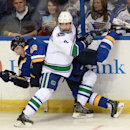 St. Louis Blues' David Backes (42) is checked by Vancouver Canucks' Dan Hamhuis (2) during the first period of an NHL hockey game, Thursday, Oct. 23, 2014, in St. Louis. The Canucks won 4-1 The Associated Press
