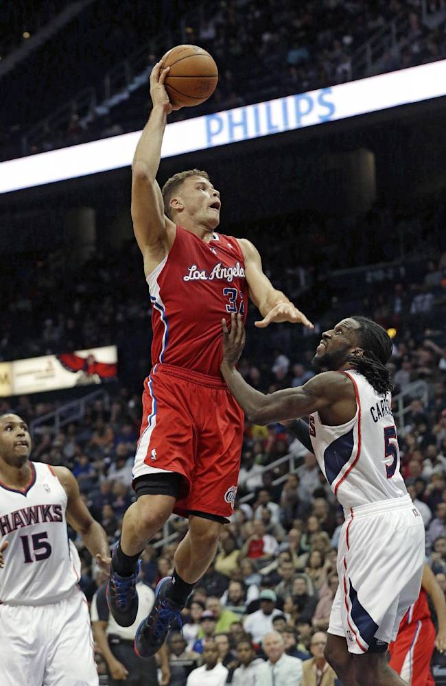 Los Angeles Clippers power forward Blake Griffin (32) scores against Atlanta Hawks small forward DeMarre Carroll (5) in the second half of an NBA  basketball game Wednesday, Dec. 4, 2013, in Atlanta.  Atlanta won 107-97