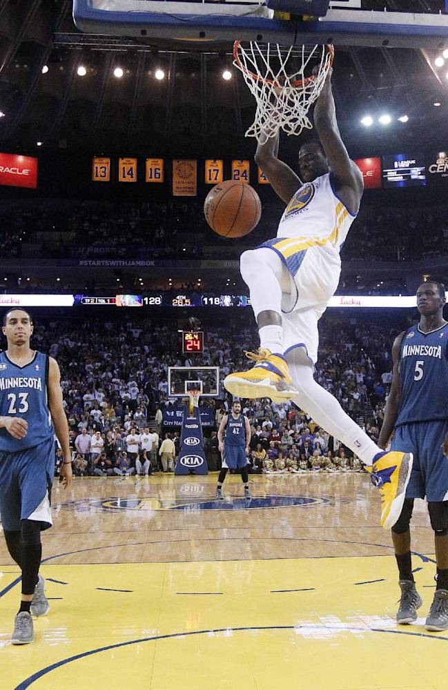 Golden State Warriors' Draymond Green, center, dunks over Minnesota Timberwolves' Kevin Martin (23) and Gorgui Dieng (5) during the second half of an NBA basketball game on Monday, April 14, 2014, in Oakland, Calif. Golden State won 130-120