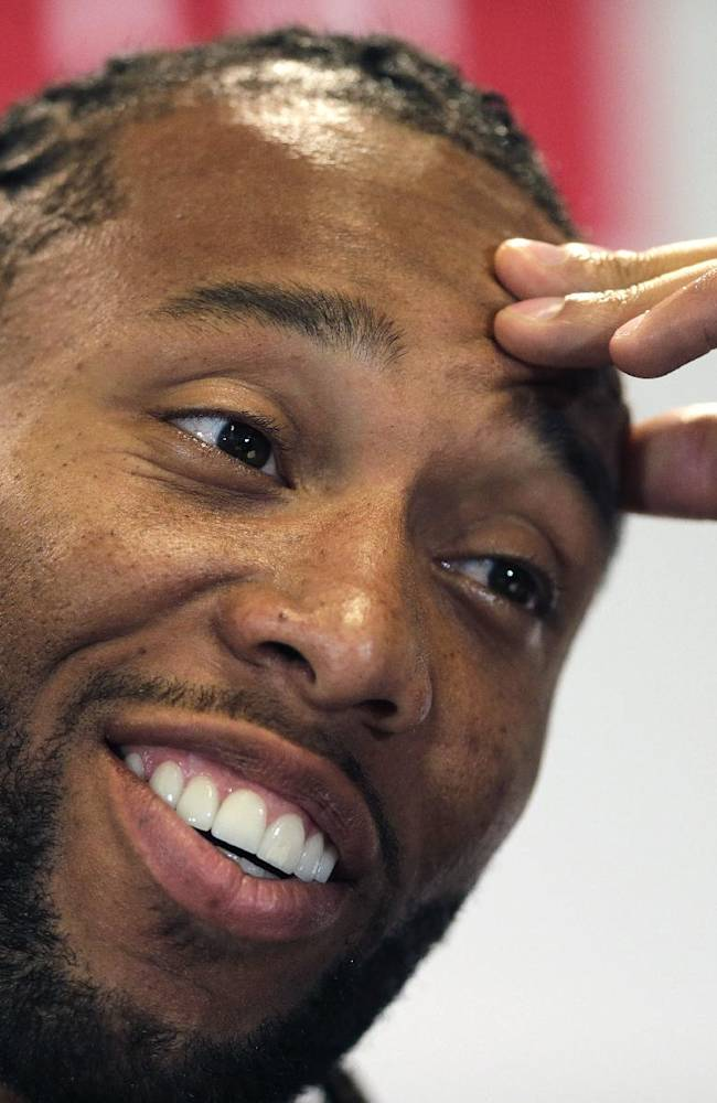 In this April 23, 2014, file photo, Arizona Cardinals wide receiver Larry Fitzgerald smiles as he answers a question during a panel discussion at Harvard University in Cambridge, Mass. There's hardly an NFL offseason anymore, but dozens of players are taking it to an extreme, choosing to hit one of several NFL academies rather than head to the beach of visit home during their rare weeks off.  Fitzgerald started a camp after his first Pro Bowl in 2005. The next thing Fitzgerald knew, quarterbacks such as the Vikings' Teddy Bridgewater and Matt Cassel were hanging around the practices