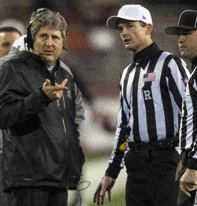 Washington State head coach Mike Leach, left, asks referee Land Clark, center, and head linesman Bart Longson, right, a question during the first half of an NCAA college football game against Arizona State, Thursday, Oct. 31, 2013, at Martin Stadium in Pullman, Wash. Arizona State won 55-21