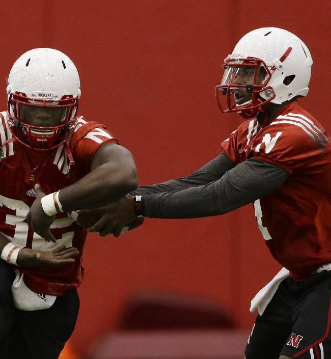 Nebraska quarterback Tommy Armstrong Jr., right, fakes a handoff to running back Imani Cross (32) on the first day of sping NCAA college football practice in Lincoln, Neb., Saturday, March 8, 2014