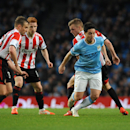 Manchester City's Samir Nasri, right, evades Sunderland's Andrea Dossena, left, Jack Colback and Sebastian Larsson during the English Premier League soccer match between Manchester City and Sunderland at The Etihad Stadium, Manchester, England, Wednesday,