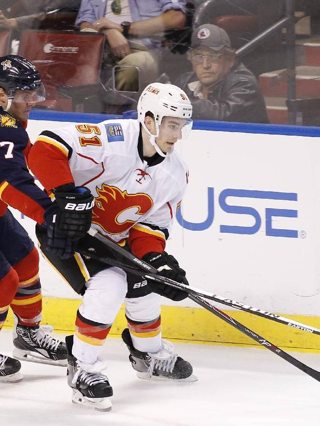 Florida Panthers defenseman Dmitry Kulikov (7) and Calgary Flames left wing Ken Agostino (51) fight for the puck during the first period of an NHL hockey game in Sunrise, Fla.,  Friday, April 4, 2014