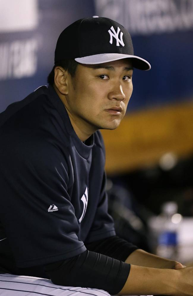 New York Yankees pitcher Masahiro Tanaka sits in the dugout during the first inning of an exhibition baseball game against the Baltimore Orioles on Tuesday, March 4, 2014, in Tampa, Fla