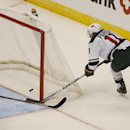 Minnesota Wild left wing Zach Parise, right, slides puck into net for empty-net goal as Colorado Avalanche defenseman Tyson Barrie covers in the third period of the Wild's 3-0 victory in an NHL hockey game in Denver on Saturday, Oct. 11, 2014 The Associat