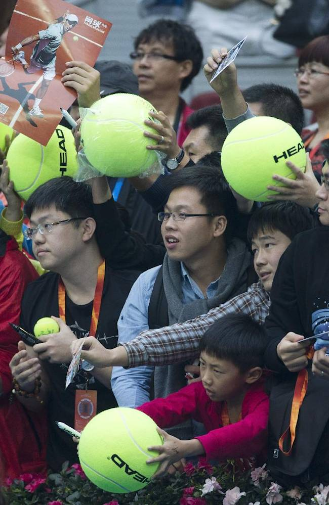 Chinese fans carry balls awaiting Novak Djokovic of Serbia to give them autographs during the China Open tennis tournament at the National Tennis Stadium in Beijing, China Thursday, Oct. 3, 2013