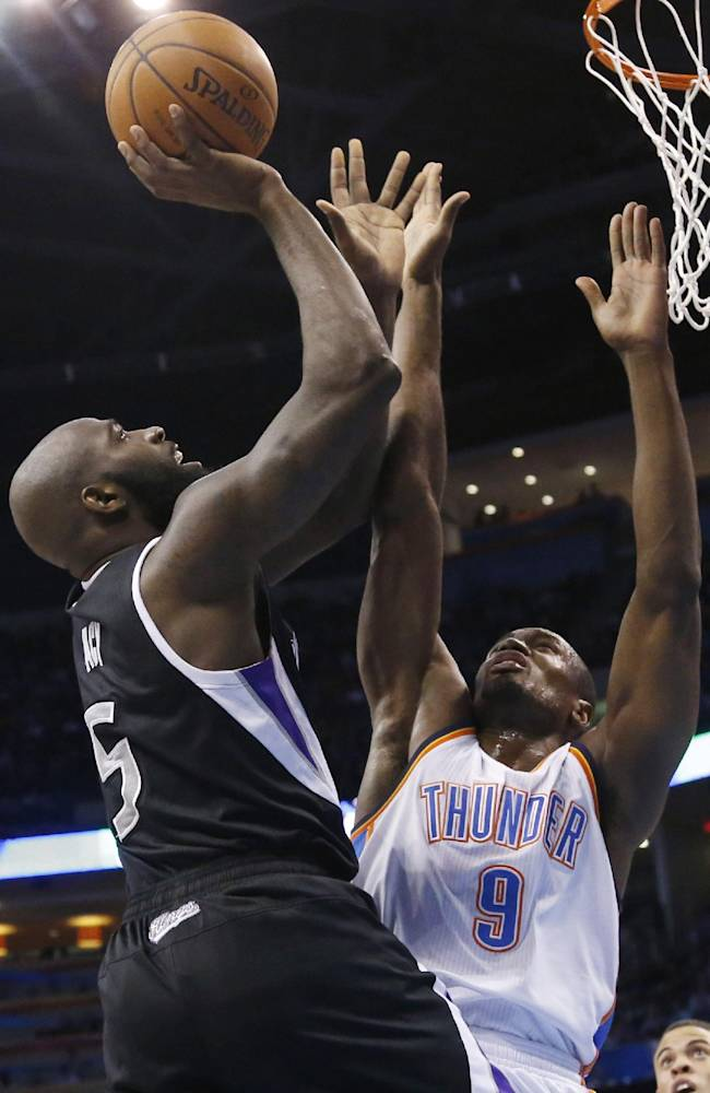 Sacramento Kings forward Quincy Acy (5) shoots in front of Oklahoma City Thunder forward Serge Ibaka (9) during the first quarter of an NBA basketball game in Oklahoma City, Friday, March 28, 2014