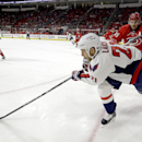 Washington Capitals' Brooks Laich (21) chases the puck against Carolina Hurricanes' Ron Hainsey (65) during the first period of an NHL hockey game in Raleigh, N.C., Thursday, Dec. 4, 2014 The Associated Press