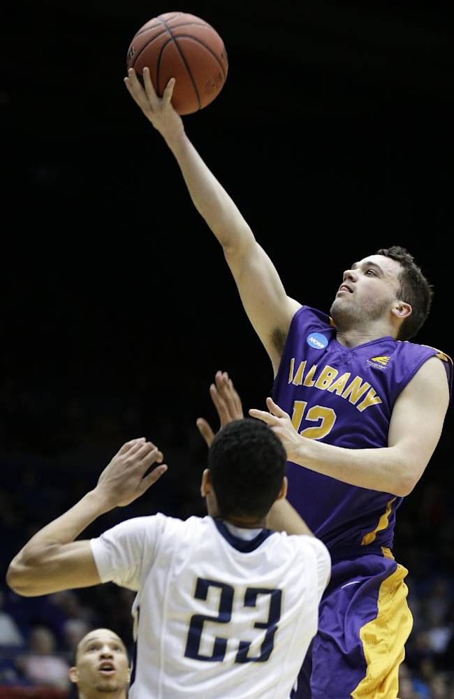 Albany guard Peter Hooley (12) drives against Mount St. Mary's guard Julian Norfleet (23) during the first half of a first-round game of the NCAA college basketball tournament, Tuesday, March 18, 2014, in Dayton, Ohio