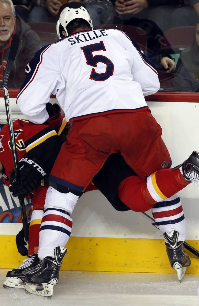Columbus Blue Jackets' Jack Skille, right, checks Calgary Flames' Jiri Hudler, from the Czech Republic, during first period NHL hockey action in Calgary, Alberta, Wednesday, Nov. 20, 2013