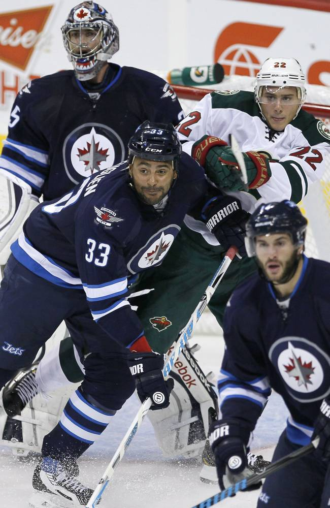 Winnipeg Jets' Dustin Byfuglien (33) and Minnesota Wild's Nino Niederreiter (22) fight for position in front of Jets' goaltender Al Montoya (35) during first-period preseason NHL hocky game action in Winnipeg, Manitoba, Thursday, Sept. 19, 2013