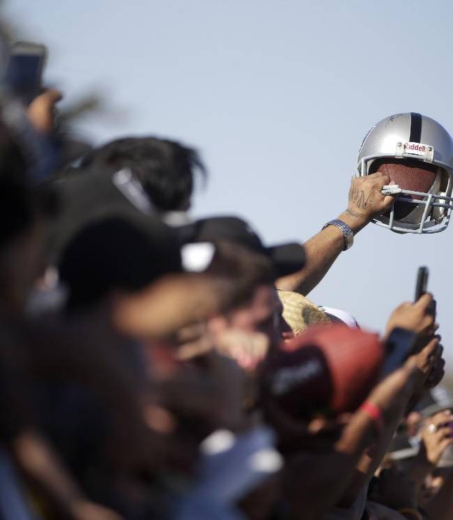 An Oakland Raiders fan holds up a helmet during the team's joint football practice with the Dallas Cowboys on Tuesday, Aug. 12, 2014, in Oxnard, Calif