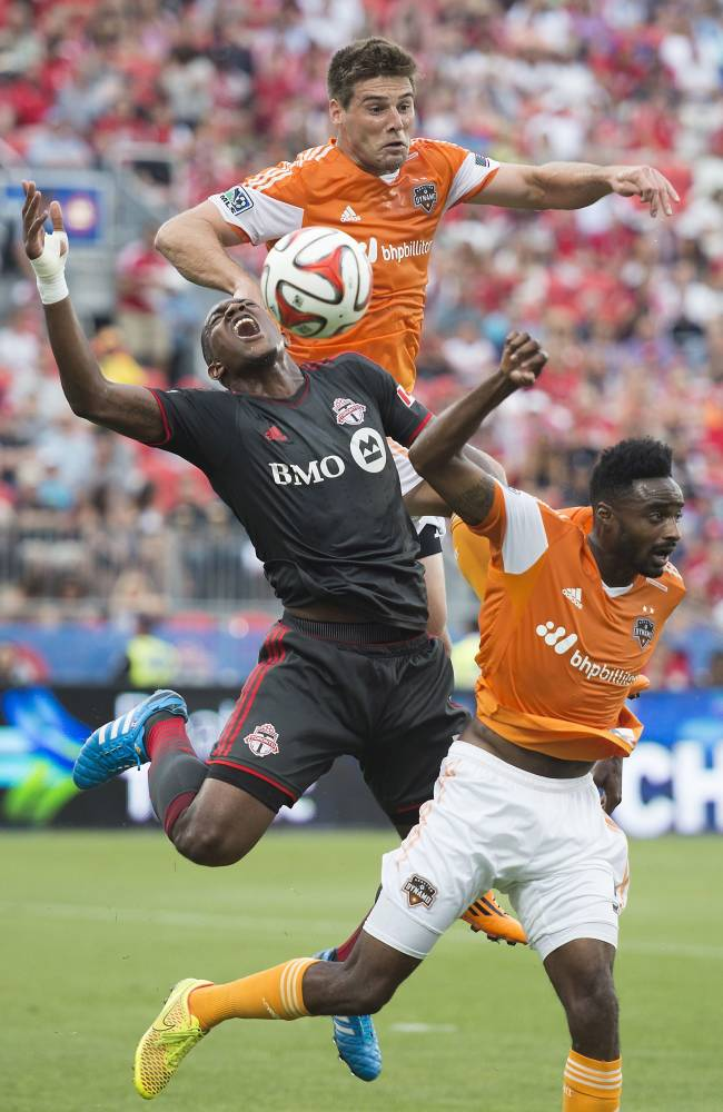Toronto FC's Doneil Henry, left, gets tangled up with Houston Dynamos David Horst, center, and Warren Creavalle while battling for the ball during an MLS soccer match in Toronto on Saturday, July 12, 2014