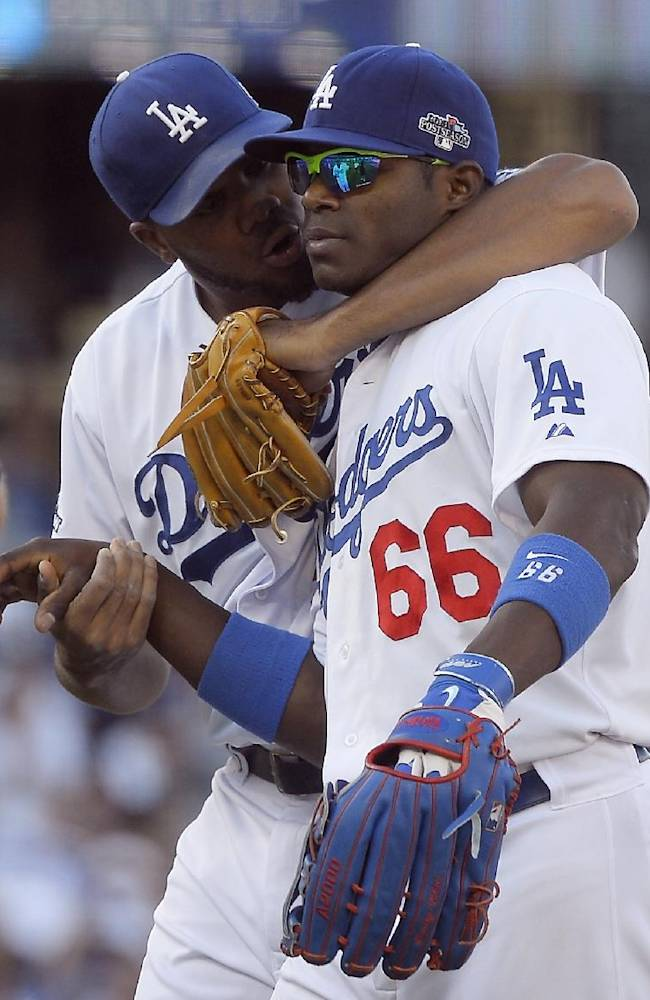 Los Angeles Dodgers' Kenley Jansen speaks with  Yasiel Puig after Game 5 of the National League baseball championship series against the St. Louis Cardinals Wednesday, Oct. 16, 2013, in Los Angeles. The Dodgers won 6-4 and trail in the series 3-2