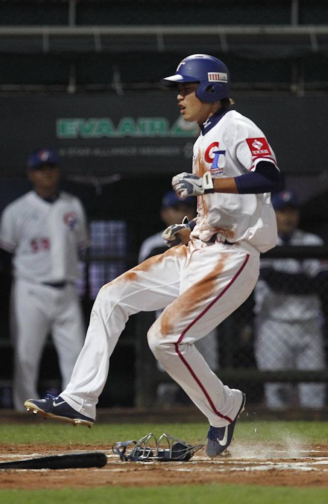 Taiwan's Chen Pin-chieh scores a run on a single by Chiang Chih-hsien against Japan in the first inning of their exhibition baseball game at the Xinzhuang Baseball Stadium in New Taipei City, Taiwan, Friday, Nov. 8, 2013