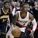 Portland Trail Blazers guard Damian Lillard, right, heads downcourt ahead of Indiana Pacers forward Paul George during the second half of an NBA basketball game in Portland, Ore., Monday, Dec. 2, 2013. Lillard scored 26 points as the Trail Blazers won 10