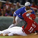 Cincinnati Reds' Joey Votto (19) slides safely into third base under the tag of Los Angeles Dodgers third baseman Juan Uribe in the first inning during an exhibition baseball game in Goodyear, Ariz., Wednesday, March 5, 2014 The Associated Press