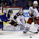 St. Louis Blues' T.J. Oshie, left, reaches for a loose puck as Columbus Blue Jackets goalie Curtis McElhinney, center, and Jerry D'Amigo, right, defend during the second period of a preseason NHL hockey game Thursday, Sept. 25, 2014, in St. Louis. The Ass