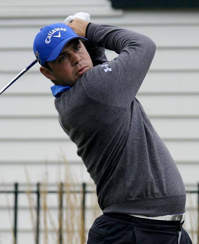 Gary Woodland watches his ball after teeing off on the third hole in the final round of the BMW Championship golf tournament at Conway Farms Golf Club in Lake Forest, Ill., Sunday, Sept. 15, 2013