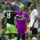 Seattle Sounders' Djimi Traore, (18), shakes hands with Tottenham Hotspur goalkeeper Brad Friedel, center, and Younes Kaboul (4) following a friendly soccer match in Seattle, Saturday, July 19, 2014. The match ended in a 3-3 draw