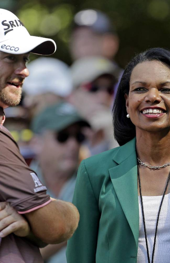 In this April 10, 2013, file photo, former Secretary of State Condoleezza Rice, right, speaks with Graeme McDowell, of Northern Ireland, during the par-3 competition at the Masters golf tournament in Augusta, Ga. A person with direct knowledge of the process tells The Associated Press on Friday, Oct. 4, 2013, that Rice is expected to be part of the selection committee that will pick the teams for the College Football Playoff next year. The person spoke on condition of anonymity because the selection process is still ongoing