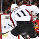 Chicago Blackhawks goalie Corey Crawford, right, keeps an eye on the puck as Colorado Avalanche left wing Jamie McGinn (11) tries to get a rebound shot during the first period of an NHL hockey game Tuesday, March 4, 2014, in Chicago The Associated Press