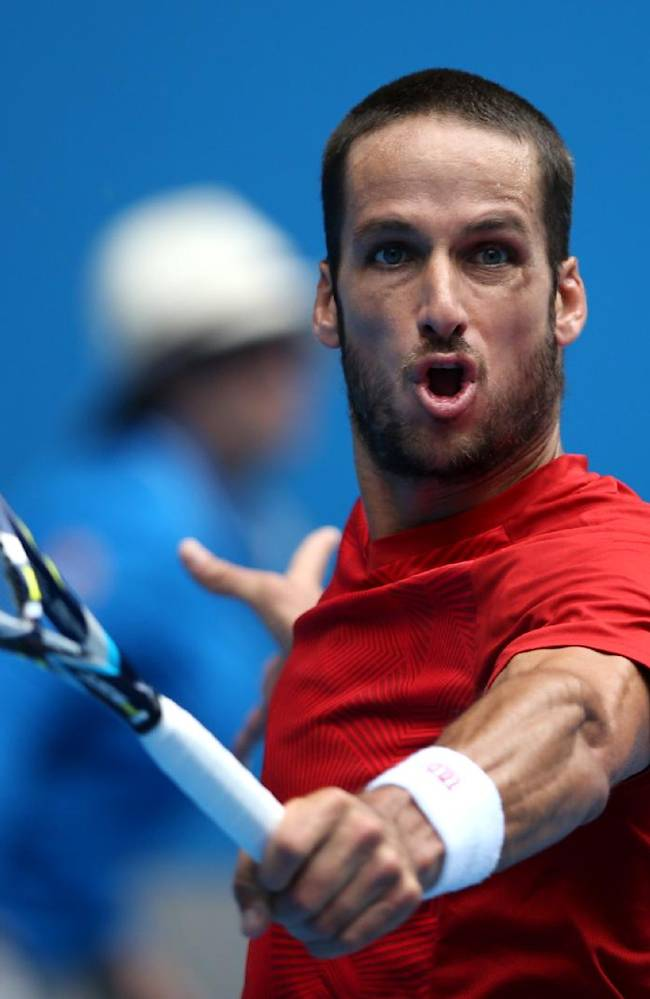 Feliciano Lopez of Spain makes a return to Andy Murray of Britain during their third round match at the Australian Open tennis championship in Melbourne, Australia, Saturday, Jan. 18, 2014